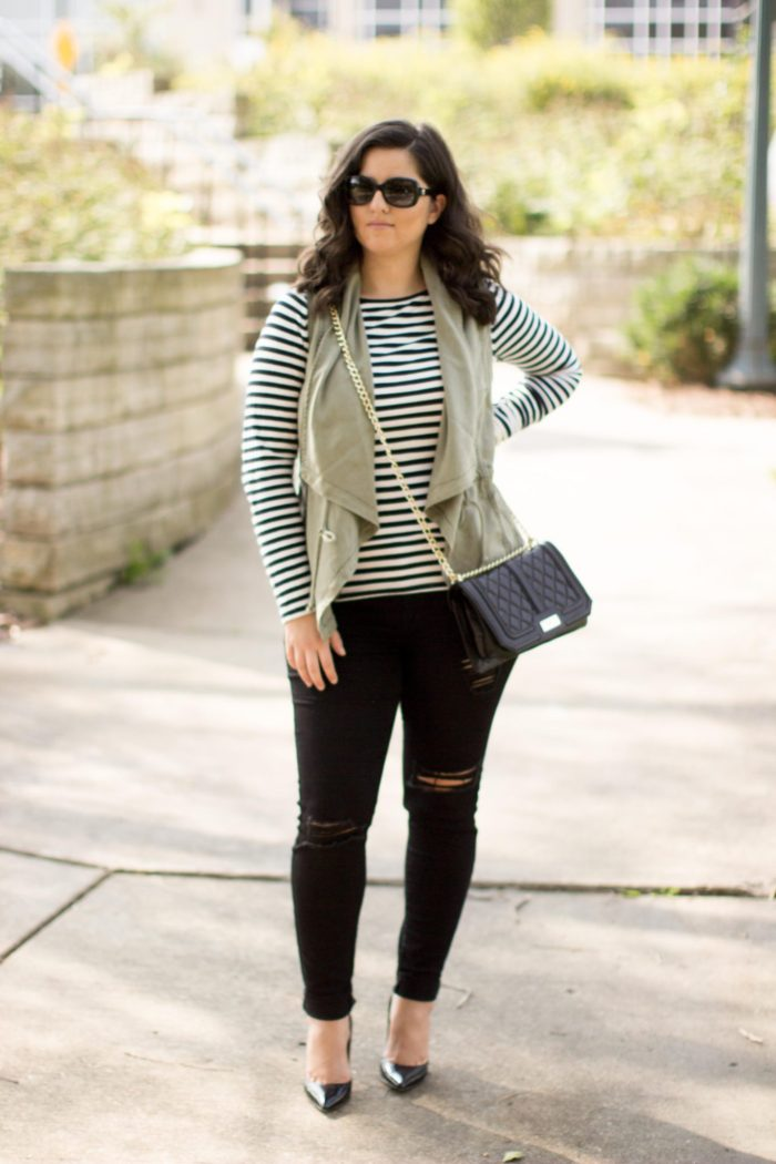 how to style a green utility vest, striped top, black skinny jeans, distressed black jeans, black quilted crossbody handbag, fall outfit idea, casual fall outfit